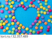 Купить «candy drops in shape of heart on blue background», фото № 32357489, снято 11 декабря 2018 г. (c) Syda Productions / Фотобанк Лори