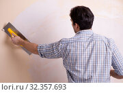 Купить «Young man applying plaster on wall at home», фото № 32357693, снято 15 марта 2018 г. (c) Elnur / Фотобанк Лори