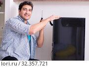 Купить «Man repairing broken tv at home», фото № 32357721, снято 9 марта 2018 г. (c) Elnur / Фотобанк Лори