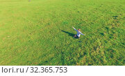 Купить «Low orbital flight around man on green grass with notebook pad at yellow rural field.», видеоролик № 32365753, снято 15 марта 2019 г. (c) Александр Маркин / Фотобанк Лори