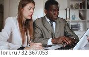 Купить «Young woman and man colleagues working with laptop and papers in office», видеоролик № 32367053, снято 26 апреля 2019 г. (c) Яков Филимонов / Фотобанк Лори