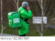 Купить «Курьер сервиса доставки еды Delivery Club принимает заказ в парке в центре города Москвы, Россия», фото № 32367061, снято 2 ноября 2019 г. (c) Николай Винокуров / Фотобанк Лори