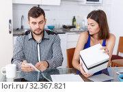 Купить «Upset young couple with bill and box having conflict at home», фото № 32367821, снято 6 июля 2018 г. (c) Яков Филимонов / Фотобанк Лори