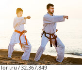 Купить «Man and boy exercising karate», фото № 32367849, снято 12 июля 2017 г. (c) Яков Филимонов / Фотобанк Лори