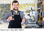Купить «smiling man worker displaying result of his key making in workshop», фото № 32367861, снято 5 апреля 2017 г. (c) Яков Филимонов / Фотобанк Лори