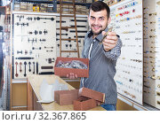 Купить «male seller sorting boxes with door handles in houseware shop», фото № 32367865, снято 5 апреля 2017 г. (c) Яков Филимонов / Фотобанк Лори