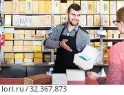Купить «seller helping female client to choose door hinges in houseware shop», фото № 32367873, снято 5 апреля 2017 г. (c) Яков Филимонов / Фотобанк Лори