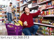 Купить «Couple standing near shelves with canned goods at store», фото № 32368013, снято 14 марта 2017 г. (c) Яков Филимонов / Фотобанк Лори
