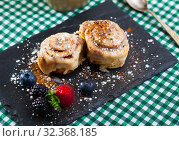 Купить «Tasty cinnamon rolls with fresh berries and powdered sugar at plate», фото № 32368185, снято 12 декабря 2019 г. (c) Яков Филимонов / Фотобанк Лори