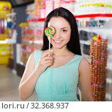 Купить «Smiling girl sucking lollypop in store», фото № 32368937, снято 25 апреля 2017 г. (c) Яков Филимонов / Фотобанк Лори