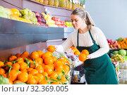 Купить «Happy female in apron selling fresh oranges», фото № 32369005, снято 1 апреля 2020 г. (c) Яков Филимонов / Фотобанк Лори