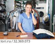 Купить «Worker of dry cleaning on reception», фото № 32369073, снято 9 мая 2018 г. (c) Яков Филимонов / Фотобанк Лори