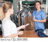 Купить «Laundry worker giving clean clothes to client», фото № 32369085, снято 9 мая 2018 г. (c) Яков Филимонов / Фотобанк Лори