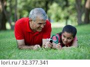 Купить «Grandfather holding flower while granddaughter looks through magnifying glass», фото № 32377341, снято 28 сентября 2012 г. (c) easy Fotostock / Фотобанк Лори