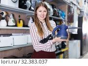 Happy saleswoman offering steam cleaner. Стоковое фото, фотограф Яков Филимонов / Фотобанк Лори
