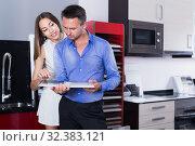 Купить «Smiling family couple looking at modern kitchen», фото № 32383121, снято 15 июня 2017 г. (c) Яков Филимонов / Фотобанк Лори