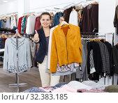 Купить «Woman holding lot of hanger with clothes», фото № 32383185, снято 10 октября 2018 г. (c) Яков Филимонов / Фотобанк Лори
