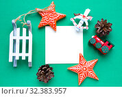 Купить «Christmas decorations and empty paper on green. Copy space. Flat lay. New Year candy, stars, toy horse, train and sled. Letter for Santa Claus, card for best wishes or to do list», фото № 32383957, снято 30 октября 2019 г. (c) Papoyan Irina / Фотобанк Лори