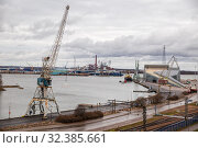 View of one of port areas of Kotka, port cranes, Sunila pulp and paper mill and Vellamo maritime centre. Редакционное фото, фотограф Юлия Бабкина / Фотобанк Лори