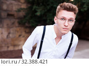 Купить «young European guy in shirt and trousers with suspenders walking around city», фото № 32388421, снято 27 июня 2018 г. (c) Татьяна Яцевич / Фотобанк Лори