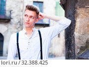 Купить «young European guy in shirt and trousers with suspenders walking around city», фото № 32388425, снято 27 июня 2018 г. (c) Татьяна Яцевич / Фотобанк Лори