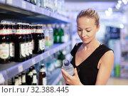 Woman choosing mineral water in grocery store. Стоковое фото, фотограф Matej Kastelic / Фотобанк Лори