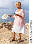 Купить «Elderly woman using phone at seaside», фото № 32389013, снято 6 июля 2018 г. (c) Яков Филимонов / Фотобанк Лори