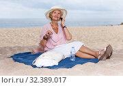 Купить «Aged woman talking on phone outdoors», фото № 32389017, снято 6 июля 2018 г. (c) Яков Филимонов / Фотобанк Лори