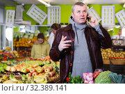 Купить «Smiling man solving questions by phone in store», фото № 32389141, снято 13 февраля 2018 г. (c) Яков Филимонов / Фотобанк Лори