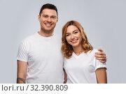 Купить «portrait of happy couple in white t-shirts», фото № 32390809, снято 6 октября 2019 г. (c) Syda Productions / Фотобанк Лори