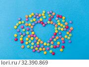 Купить «candy drops in shape of heart on blue background», фото № 32390869, снято 11 декабря 2018 г. (c) Syda Productions / Фотобанк Лори
