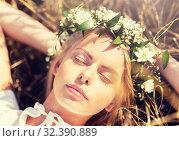 Купить «happy woman in wreath of flowers lying on straw», фото № 32390889, снято 31 июля 2016 г. (c) Syda Productions / Фотобанк Лори
