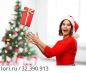 Купить «happy young woman in santa hat catching gift box», фото № 32390913, снято 30 сентября 2019 г. (c) Syda Productions / Фотобанк Лори