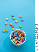 Купить «candy drops in paper cup on blue background», фото № 32390945, снято 11 декабря 2018 г. (c) Syda Productions / Фотобанк Лори