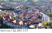 Купить «Aerial view of historical centre of Cesky Krumlov town on Vltava riverbank on autumn day overlooking medieval Castle, Czech Republic», видеоролик № 32391117, снято 12 октября 2019 г. (c) Яков Филимонов / Фотобанк Лори