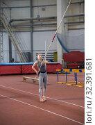 Купить «Pole vaulting indoors - young woman holding a pole looking up on it», фото № 32391681, снято 1 ноября 2019 г. (c) Константин Шишкин / Фотобанк Лори
