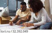Купить «couple with blueprint and color palettes at home», видеоролик № 32392049, снято 3 ноября 2019 г. (c) Syda Productions / Фотобанк Лори