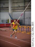 Купить «Pole vaulting - man in yellow shirt is running with a long pole in hands», фото № 32396381, снято 1 ноября 2019 г. (c) Константин Шишкин / Фотобанк Лори