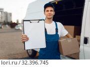 Deliveryman in uniform holding parcel, delivery. Стоковое фото, фотограф Tryapitsyn Sergiy / Фотобанк Лори