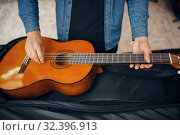 Купить «Guitarist puts guitar in the case, music store», фото № 32396913, снято 11 сентября 2019 г. (c) Tryapitsyn Sergiy / Фотобанк Лори