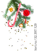 Christmas decorations and tree branch on white background. Striped candy, pompon, golden bell, present, ball and confetti. Flat lay. New Year and Christmas mood. Стоковое фото, фотограф Papoyan Irina / Фотобанк Лори