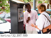 Купить «Polite intelligent African man helping middle aged woman to buy ticket in parking meter on summer city street», фото № 32397189, снято 16 февраля 2020 г. (c) Яков Филимонов / Фотобанк Лори