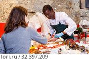 Купить «Salesman serving customer raw fish», фото № 32397209, снято 17 октября 2018 г. (c) Яков Филимонов / Фотобанк Лори