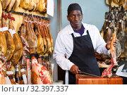 Купить «Salesman cutting delicious ham in butcher shop», фото № 32397337, снято 9 января 2019 г. (c) Яков Филимонов / Фотобанк Лори