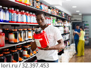 Купить «Focused muscular African man choosing sports nutrition products in shop, reading content label», фото № 32397453, снято 8 декабря 2019 г. (c) Яков Филимонов / Фотобанк Лори