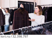 Купить «woman choosing sheepskin coat in women's cloths store», фото № 32398797, снято 23 февраля 2020 г. (c) Яков Филимонов / Фотобанк Лори