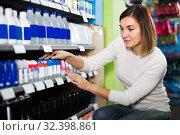 Купить «Young female shopper searching for deodorants in supermarket», фото № 32398861, снято 23 ноября 2016 г. (c) Яков Филимонов / Фотобанк Лори