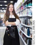 Купить «Young cheerful female hairstylist in apron in cosmetics studio», фото № 32398905, снято 31 марта 2018 г. (c) Яков Филимонов / Фотобанк Лори