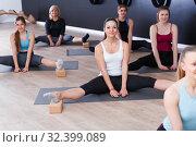 Купить «Females exercising during yoga class», фото № 32399089, снято 29 января 2018 г. (c) Яков Филимонов / Фотобанк Лори