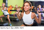 Купить «Portrait of sporty women exercising with barbell in fitness club», фото № 32399101, снято 26 июля 2017 г. (c) Яков Филимонов / Фотобанк Лори